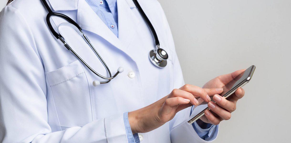unrecognizable-doctor-using-smartphone-on-white-st-DLKHN8M